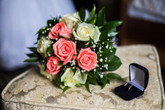 Wedding rings on blue box, wedding bands, bouquet of pink and white roses, Stock Photo
