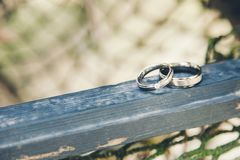 Wedding rings on a blue piece of wood stock photography