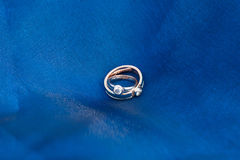 Wedding rings on the blue textile Stock Image