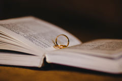 Wedding rings on a book Stock Photos