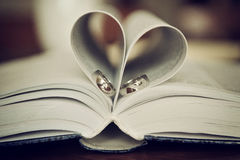 Wedding rings on a book in heart of pages Royalty Free Stock Images