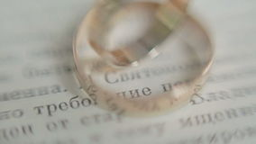 Wedding rings on a book page. stock video footage