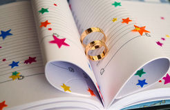 Wedding rings on a book Royalty Free Stock Images