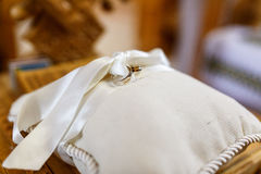 Wedding rings bounded with white ribbon lie on a pillow stock image