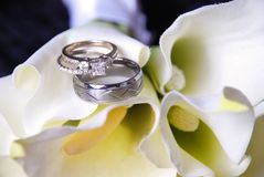 Wedding rings on bouquet. Bride and groom wedding bands on calla lillies bridal bouquet Royalty Free Stock Images