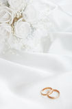 The wedding rings and a bouquet of the bride Stock Photography