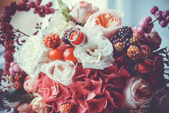Wedding rings on a bouquet of colorful flowers. With berries stock image