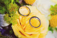 Wedding rings on a bouquet of colorful flowers Stock Photography