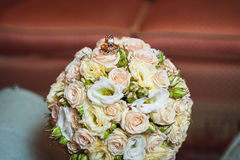 Wedding rings on a bouquet of cream roses Royalty Free Stock Photography