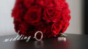 Wedding rings and bouquet. Engagement ring and bride`s bouquet and the words wedding day stock video footage