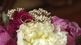Wedding rings on a bouquet of flowers. Close stock video