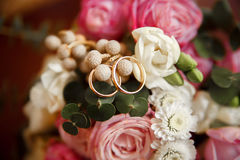 Wedding rings on a bouquet of flowers. Gold wedding rings on bouquet of roses, daisies and decorative greens Stock Photo