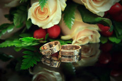 Wedding rings with bouquet. Focus on the rings Royalty Free Stock Photo