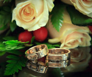 Wedding rings with bouquet. Focus on the rings Stock Photo