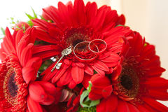 Wedding rings on the bouquet. Gold wedding rings on a red bridal bouquet Stock Photo