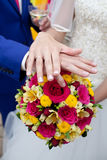 Wedding rings on the bouquet. The newlyweds show their wedding rings Stock Photos