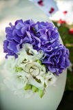 Wedding rings on the bouquet. Pair of wedding rings on the bouquet of white and purple flowers Stock Photo