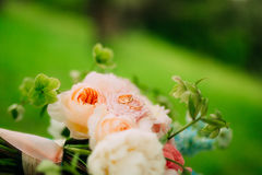 Wedding rings on a bouquet of peonies. Wedding jewelry Stock Photography