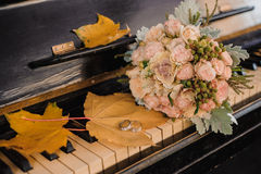Wedding rings and bouquet on piano Stock Image