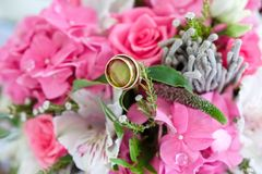 Close-up wedding rings in the bouquet of pink flowers. Wedding rings in the bouquet of pink flowers Royalty Free Stock Images