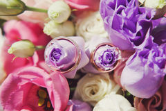 Wedding rings on a bouquet of pink flowers Stock Photo
