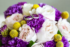 Wedding rings on bouquet of pink and purple flowers Royalty Free Stock Image