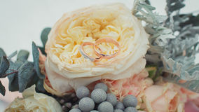 Wedding rings on a bouquet of roses.  Royalty Free Stock Photos