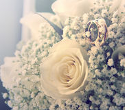 Wedding rings on a bouquet of roses. Wedding rings on a bouquet of cream roses Stock Images