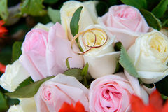 Wedding rings on a bouquet of roses. Golden rings on a wedding bouquet of roses Stock Photo