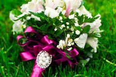 Wedding rings bouquet of roses. Golden wedding rings bouquet of white roses on green grass close-up Royalty Free Stock Image