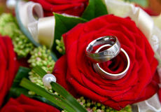 Wedding rings in bouquet of roses. Wedding bouquet with red roses and rings Royalty Free Stock Image
