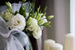 Wedding rings and bouquet of roses. Two platinum wedding rings, bouquet of white roses and candles Royalty Free Stock Images