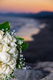 Wedding rings and bouquet at sunset Stock Photos