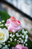 Wedding rings and bouquet on the table Stock Photography