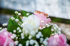 Wedding rings and bouquet on the table Royalty Free Stock Images
