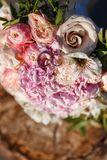 Wedding rings with bouquet on a tree stump.  Stock Photos