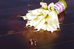 Wedding rings and a bouquet of white lilies Stock Images