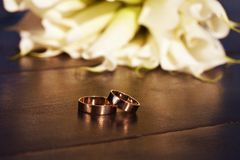 Wedding rings and a bouquet of white lilies Royalty Free Stock Images