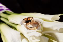 Wedding rings and a bouquet of white lilies Stock Photography