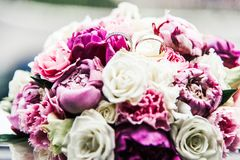 Wedding rings on bouquet of white, purple and pink peonies, close-up stock images