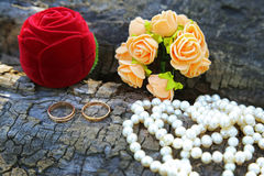 Wedding rings, boutonniere and a string of pearls Stock Photo