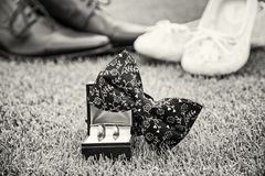 Wedding rings, bow tie and women`s and men`s shoes, colorless Royalty Free Stock Photography