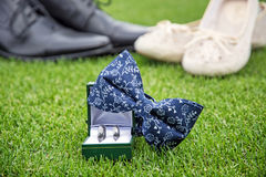 Wedding rings, bow tie and women`s and men`s shoes on the green Royalty Free Stock Photo