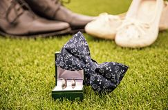 Wedding rings, bow tie and women`s and men`s shoes, yellow filte Stock Image