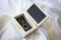 Wedding rings in a box. Picture of wedding rings placed in an opened wooden box. One of the rings is separated in two parts, one for the engagement and the other Royalty Free Stock Image