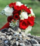 Wedding rings and bridal bouquet Stock Images