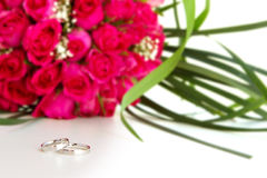 Wedding rings and bridal bouquet isolated over whi Royalty Free Stock Images