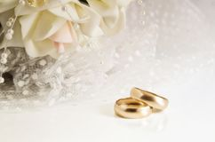 Wedding rings and bridal bouquet on a light background. Horizontal format. Indoors. Without people. Color. Photo Royalty Free Stock Image