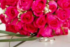 Wedding rings and bridal bouquet  over whi Royalty Free Stock Photography