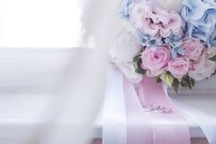 Wedding rings and bridal bouquet. On window sill Royalty Free Stock Images